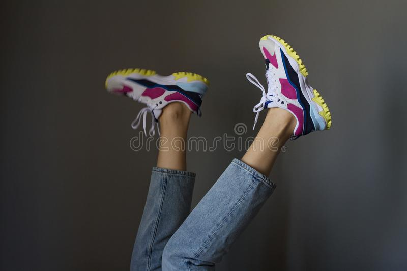 Tanned beautiful legs of a slim young woman in trendy skinny blue jeans and new colorful sport sneakers on a gray background. royalty free stock photos