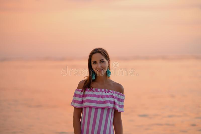 Tanned beautiful woman in dress with white and pink stripes. Orange sea or ocean at the sunset. Vacations concept stock photos