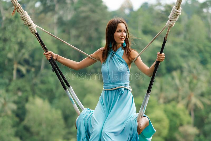 Tanned beautiful woman in a long turquoise dress with a train, riding on a swing. In the background, a rainforest and palm trees. royalty free stock image