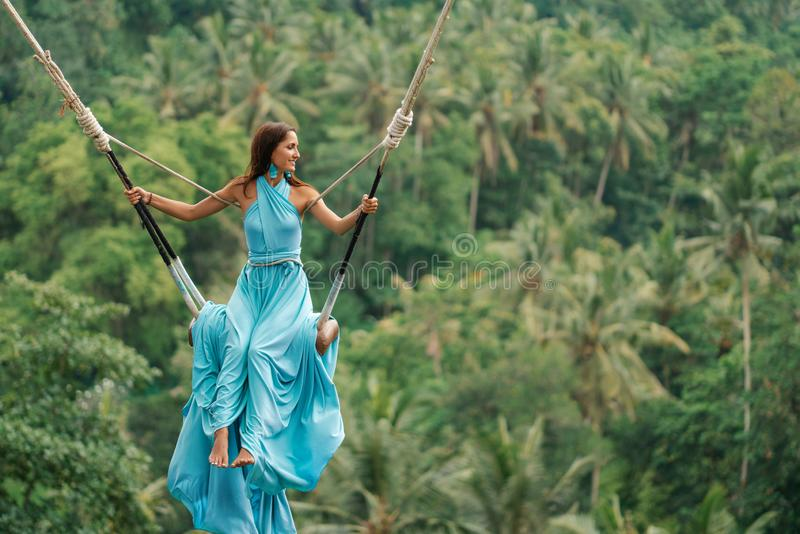 Tanned beautiful woman in a long turquoise dress with a train, riding on a swing. In the background, a rainforest and palm trees. stock images