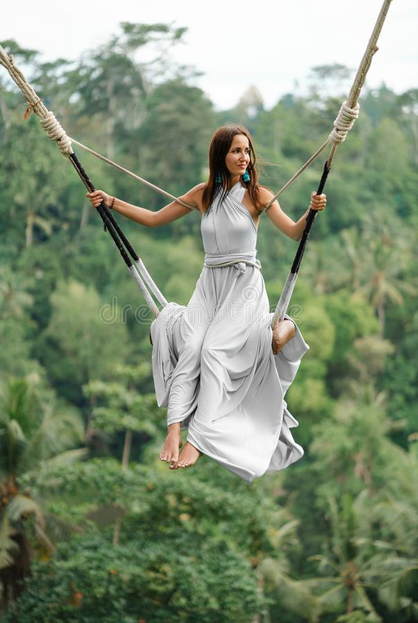 Tanned beautiful woman in a long white dress with a train, riding on a swing. In the background, a rainforest and palm trees. stock images