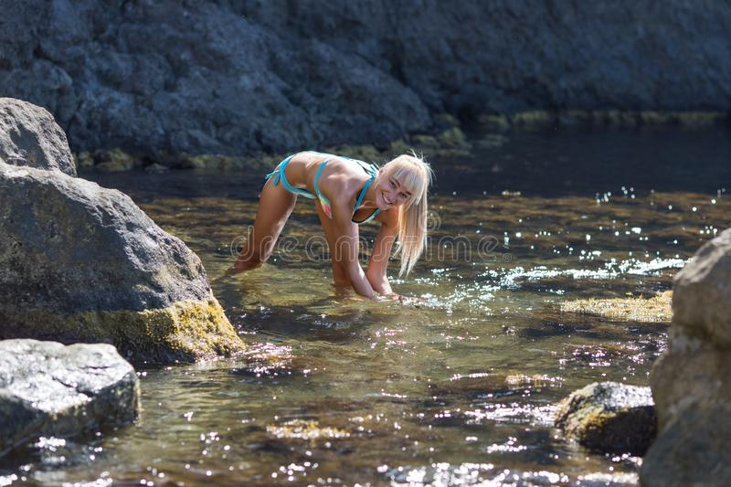 Tanned blond haired female person resting at secluded place of wild rocky seashore stock images