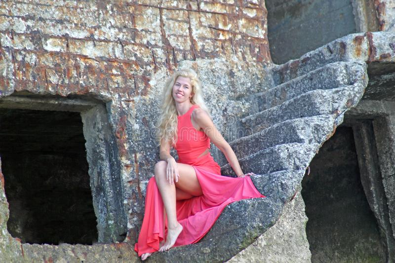 Tanned blonde girl in a red dress sitting on the stone ruins of an old fort stock photos