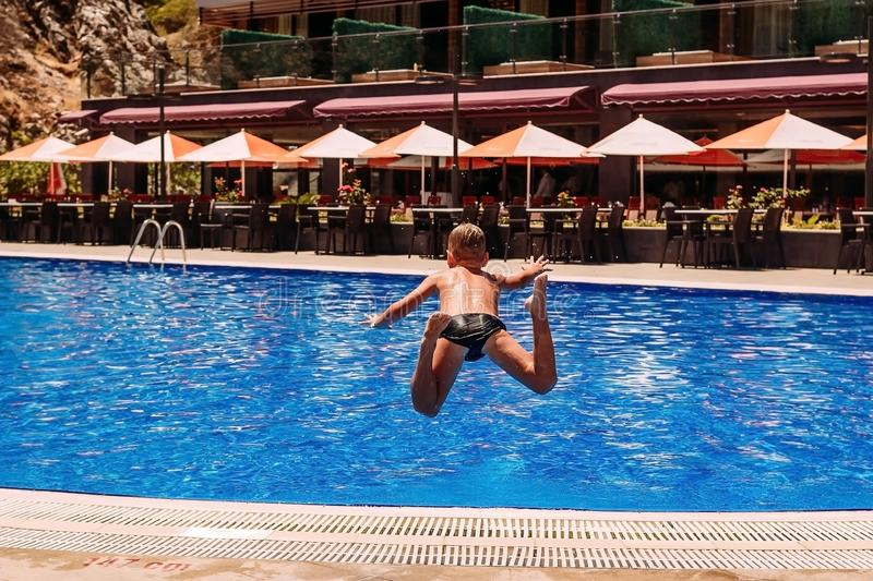 Tanned boy jumps with a run in the outdoor summer pool , rear view. Tanned boy jumps with a run in the outdoor summer pool stock image
