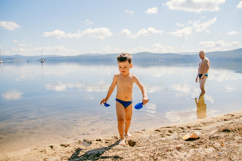 Tanned boy of three years in swimming trunks plays on the lake in the summer, summer vacation royalty free stock photo