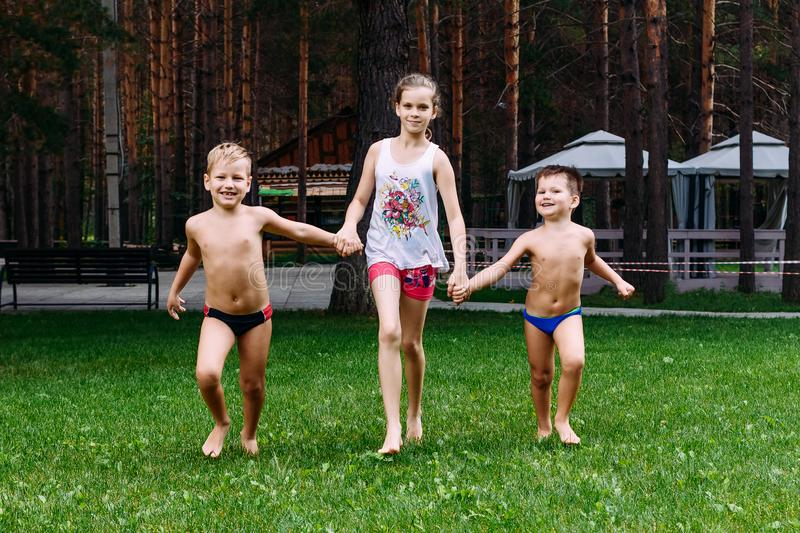 Tanned cheerful children run barefoot on the green grass on vacation in the hot summer stock image