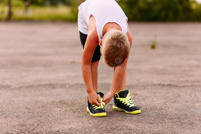 Tanned child tying shoelaces on sports shoes in the summer. Children and sports stock photography