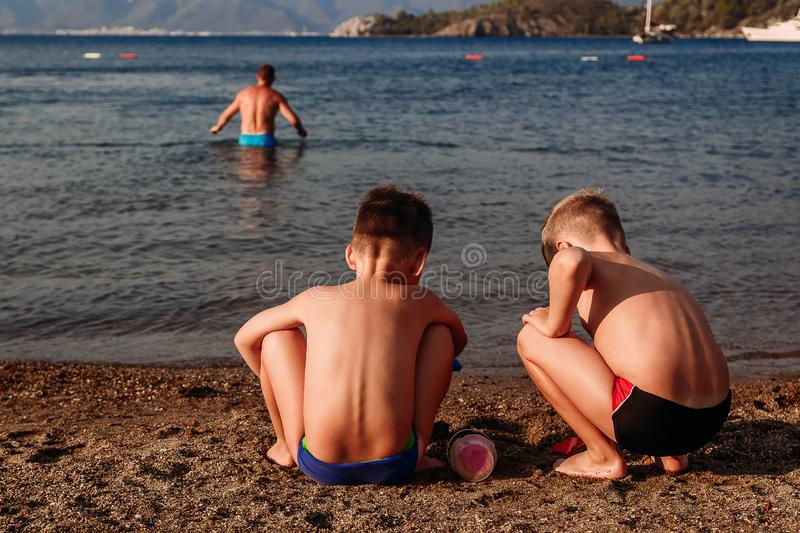 Tanned children playing with sand on the beach royalty free stock photo