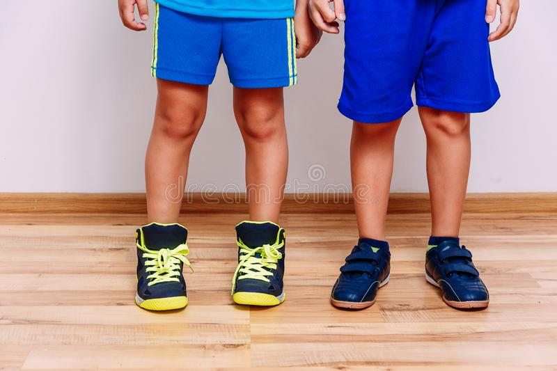 Tanned children`s feet in sports sneakers royalty free stock image