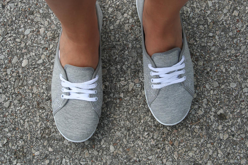 Tanned feet in gray summer shoes royalty free stock image