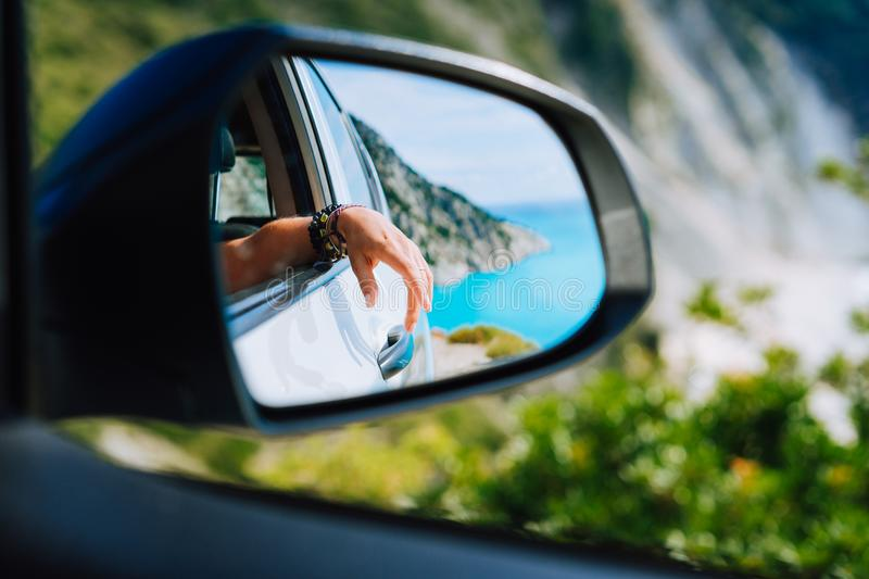 Tanned female hand in the car side view mirror. Blue mediterranean sea and white rocks landscape in background royalty free stock photo