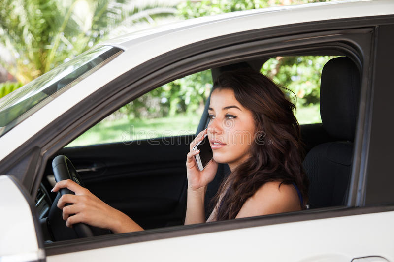 Tanned female talks on mobile phone while driving royalty free stock photography