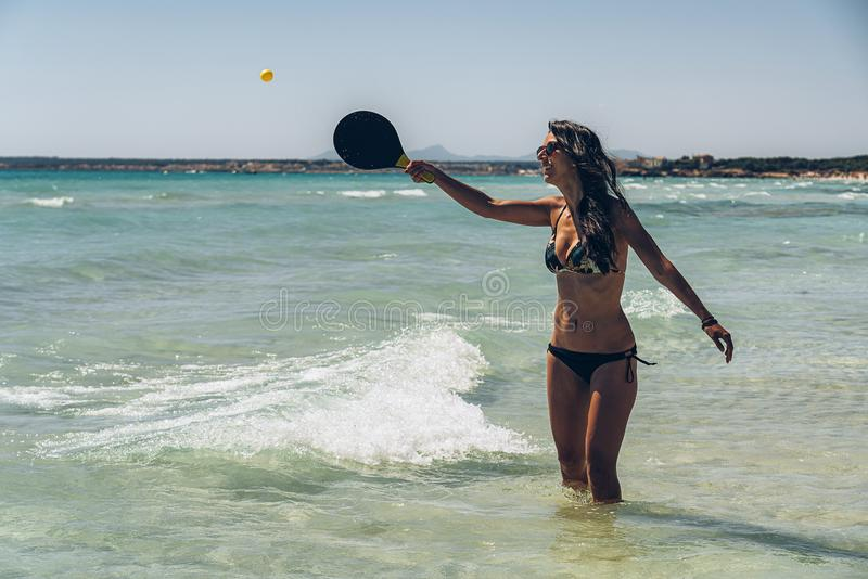 Tanned girl playing tennis in a paradise beach stock photos