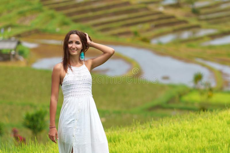Tanned woman in a white dress posing on the background of rice fields. Close up stock image