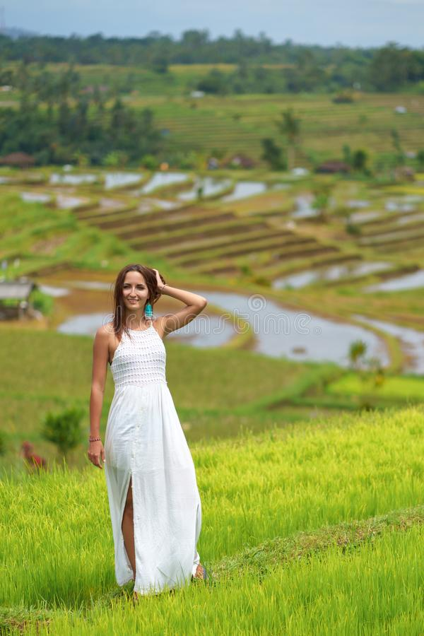 Tanned girl in a white dress posing on the background of rice fields royalty free stock photos