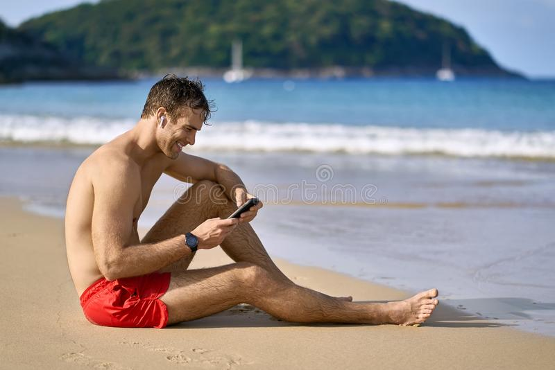 Tanned guy on beach. Attractive tanned man sits on the sand beach on the sunny background of the sea with white boats and the green hills. He wears a red swim stock images