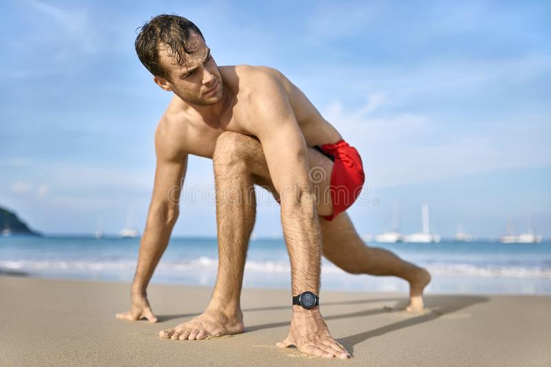 Tanned guy on beach. Cute tanned man on the sand beach on the sunny background of the sea with white boats and the blue sky. He wears a red swim trunks and a stock image