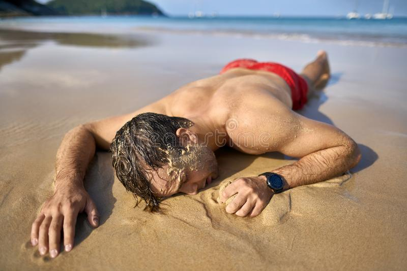 Tanned guy on beach. Cute tanned man with closed eyes lies on the stomach on the sand beach on the sunny background of the sea with white boats and the blue sky royalty free stock images