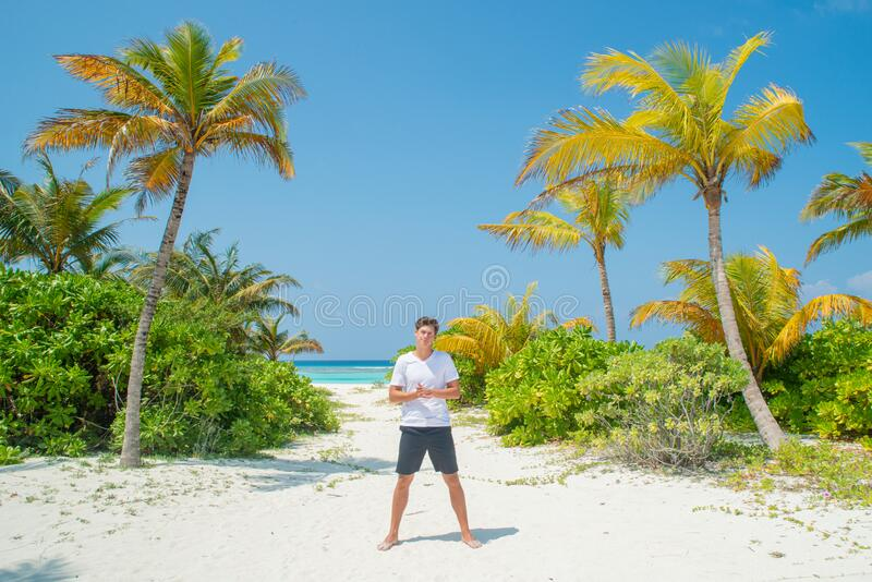 Tanned handsome man wearing white t-shirt and black shorts standing at tropical sandy beach at island luxury resort royalty free stock image