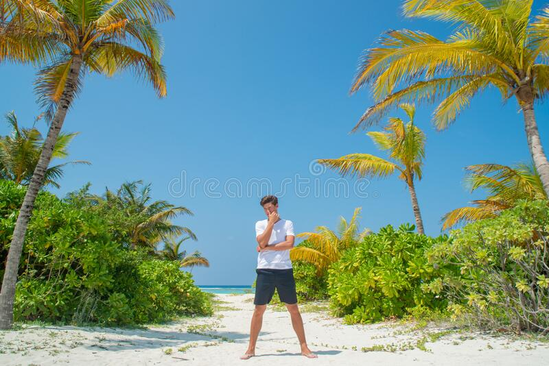 Tanned handsome man wearing white t-shirt on the tropical beach at the island luxury resort royalty free stock image