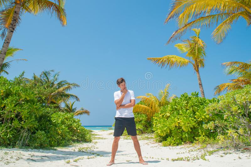 Tanned handsome young man wearing white t-shirt and black shorts standing at tropical sandy beach at island luxury resort royalty free stock image