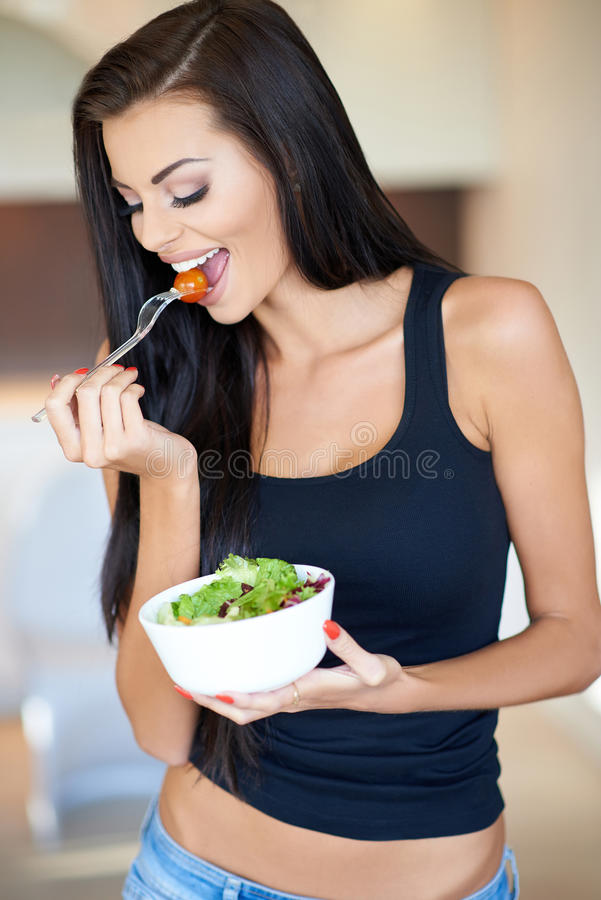 Tanned healthy young woman enjoying a mixed salad stock photography