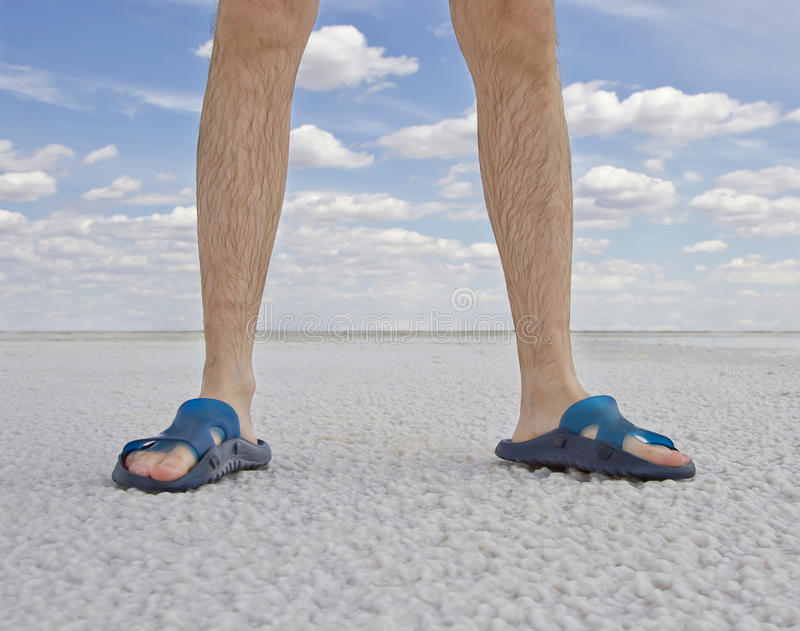 Tanned legs of man wearing flip flops. Standing on the beach stock photo