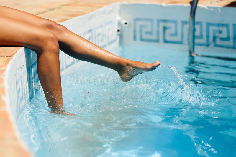 Legs of a woman enjoying playing with water of a swimming pool spa stock images