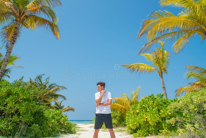 Tanned man wearing white t-shirt on the tropical beach at the island luxury resort royalty free stock images