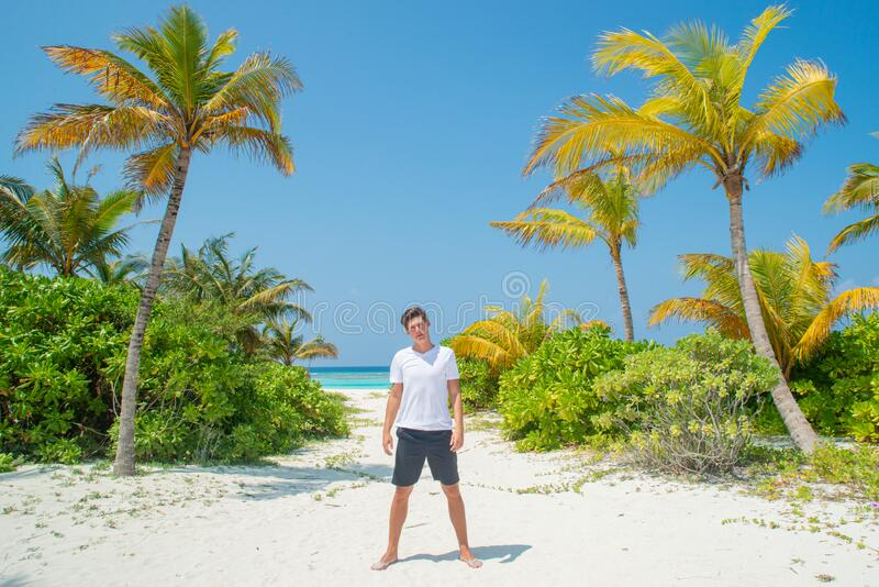 Tanned sexy young man wearing white t-shirt and black shorts standing at tropical sandy beach at island luxury resort stock photos
