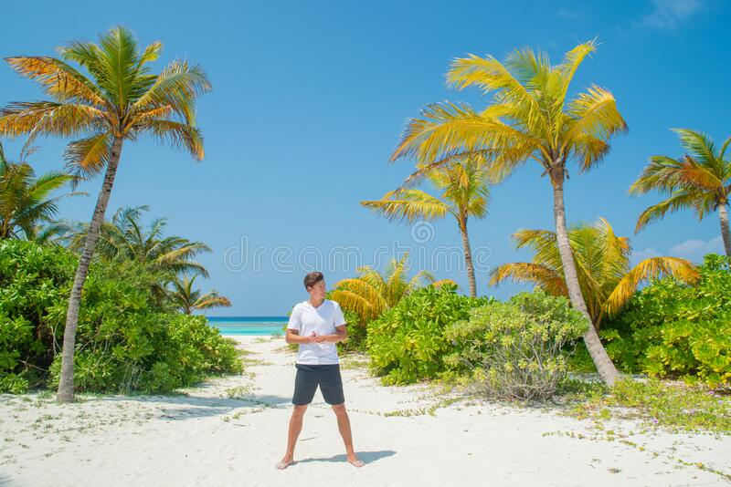 Tanned tall handsome man wearing white t-shirt and black shorts standing at tropical sandy beach at island luxury resort royalty free stock photos