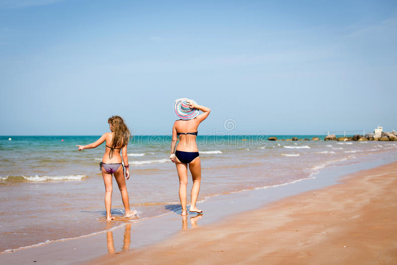 Tanned woman and girl walking on the beach stock photos