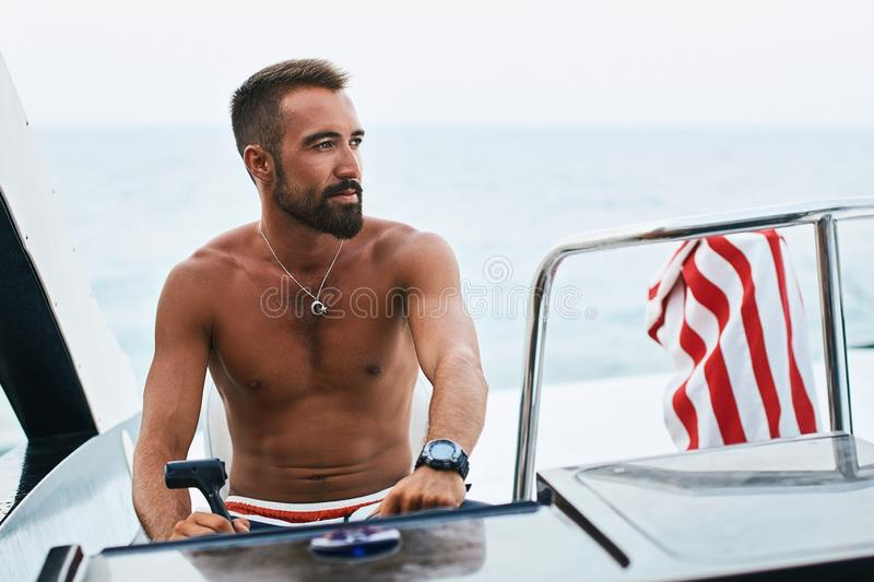 Tanned young handsome bearded muslim captain or skipper steering at the helm and control panel of a yacht looking at the stock photography