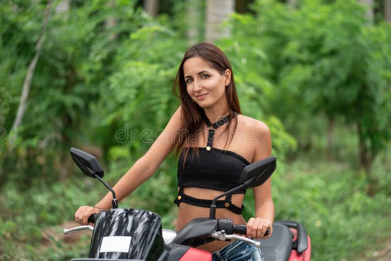 Tanned, young woman with a smile posing sitting on a motorcycle stock image