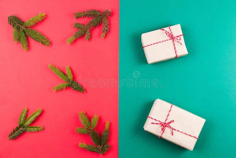 Tannenbaumast und kleine Geschenke auf rotem und grünem Hintergrund Draufsicht, flache Lage Weihnachtszusammensetzung lizenzfreie stockfotografie