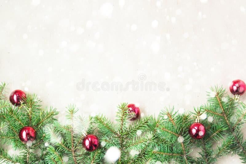 Tannenbaumaste verziert mit roten Weihnachtsbällen als Grenze auf einem rustikalen Feiertagshintergrundrahmen mit Schneekopienrau lizenzfreie stockfotos