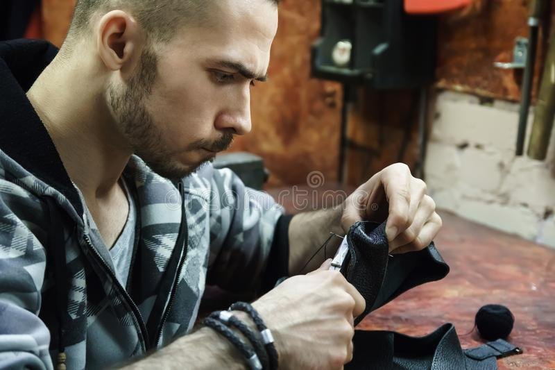 Tanner sews item in workspace royalty free stock images