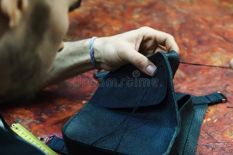 Tanner sews leather item stock image