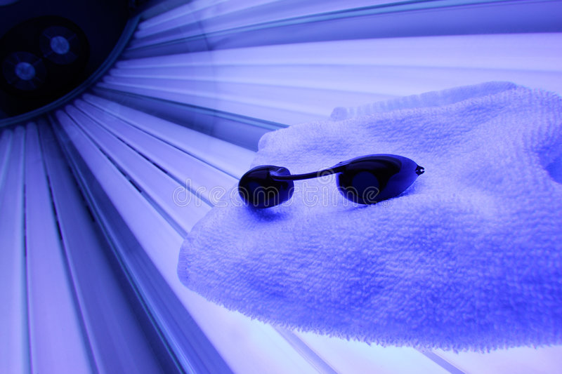 Tanning Bed. With Purple lights showing with a towle and goggles on it stock photography