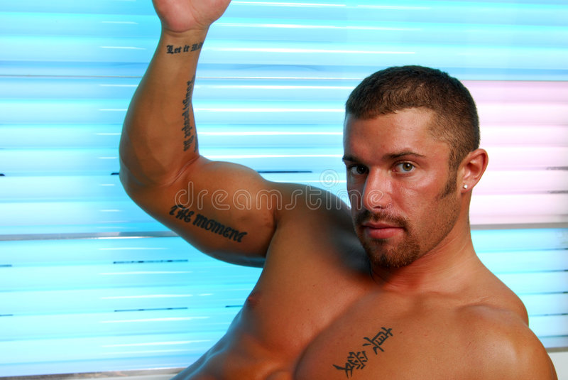 Tanning Bed. A muscular man in a tanning bed royalty free stock photography