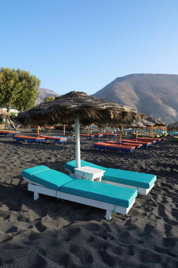 Tanning beds and umbrellas on Perissa beach, Santorini, Greece royalty free stock images
