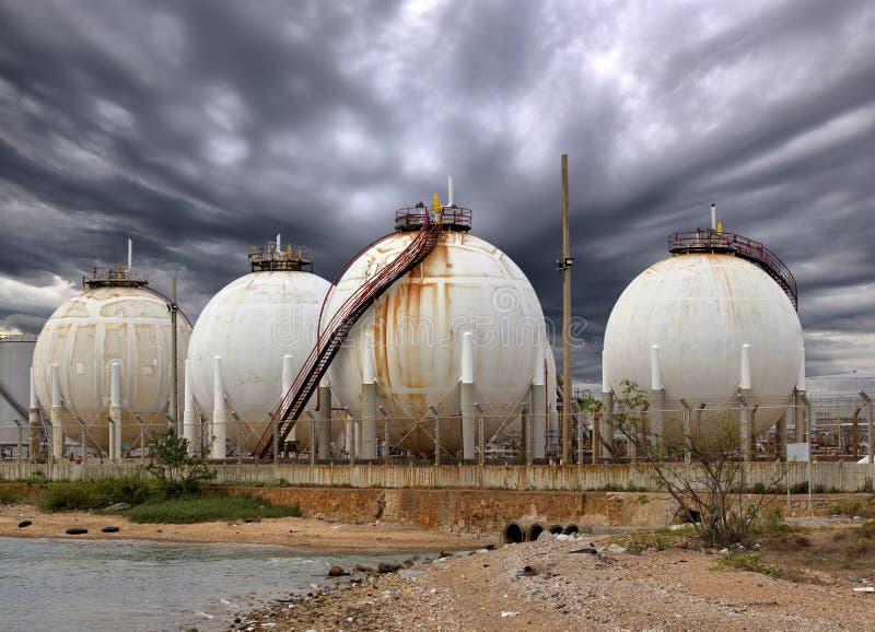 Tanques de óleo industriais grandes em uma refinaria e em um sistema de drenagem com imagens de stock royalty free