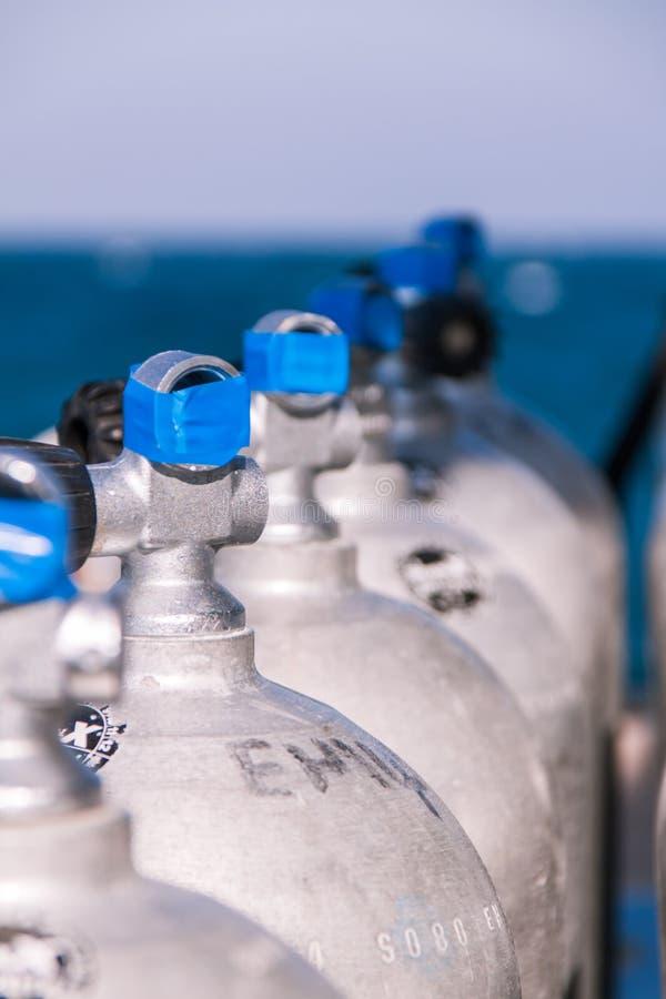 Tanques do mergulho autônomo com fita e o mar azuis no fundo foto de stock royalty free