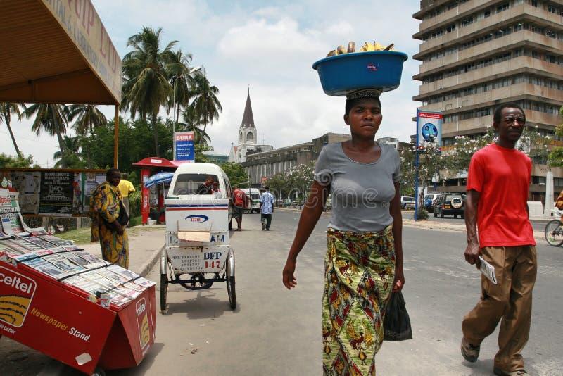 Tansanische Schwarzafrikanerfrau trägt Fracht auf Ihrem Kopf stockfotos