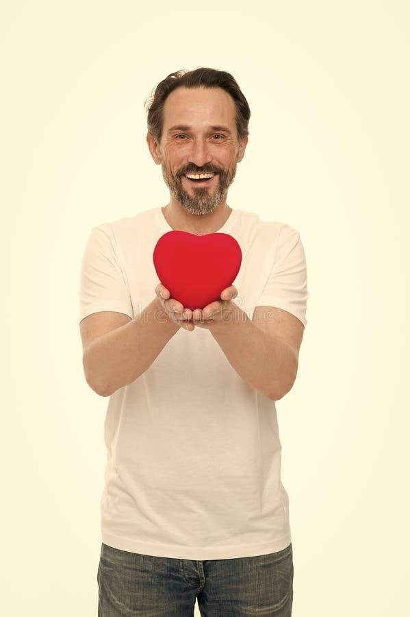 ?tant dans l'amour Homme de valentines tenant le coeur rouge de jouet dans des mains Homme m?r bel avec le coeur de jour de valen photographie stock
