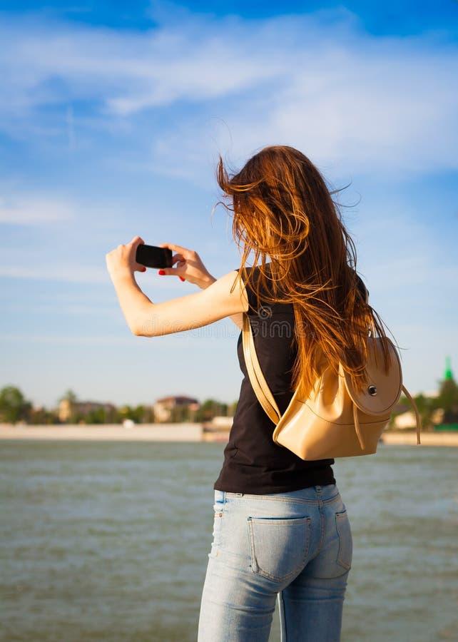 tanya fiume turistico posteriore con lo Smart Phone fotografia stock libera da diritti