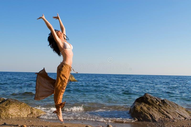 Tanz der jungen Frau im Strand stockfotos
