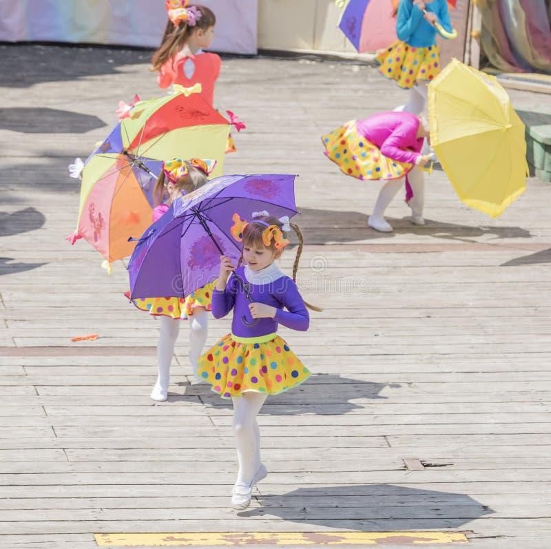 Tanz der Mädchen mit farbigen Regenschirmen am Karneval lizenzfreies stockfoto