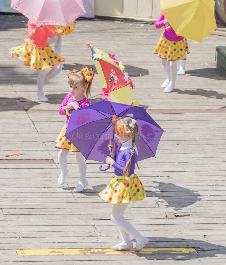 Tanz der Mädchen mit farbigen Regenschirmen am Karneval stockbilder