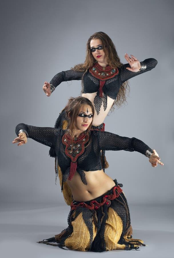 Tanz mit zwei Frauen im Krieger cosutme lizenzfreie stockfotografie